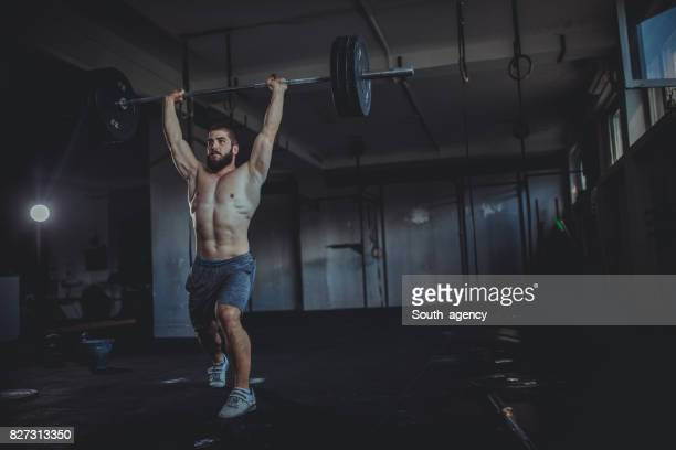 athlete lifting weights - snatch weightlifting stock photos and pictures