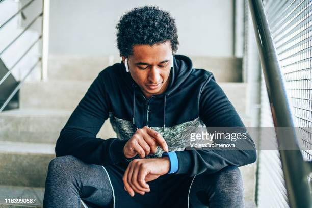 athlete looking at his smart watch - wearable computer stock pictures, royalty-free photos & images