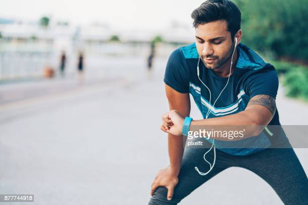 athlete looking at his smart watch - watch what happens: live stock pictures, royalty-free photos & images
