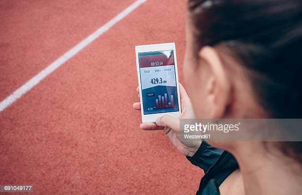 Athlete looking on smartphone with training data on display