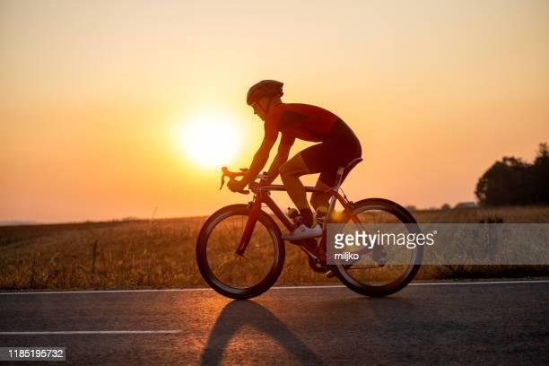 homem do atleta que monta a bicicleta na estrada - ciclismo - fotografias e filmes do acervo