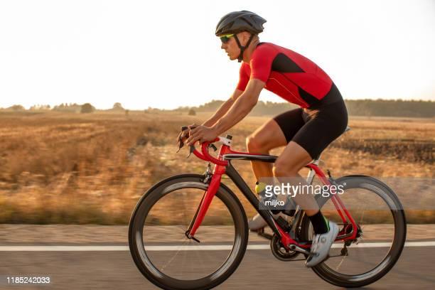 athlete man riding bicycle on the road - bicicletta da corsa foto e immagini stock