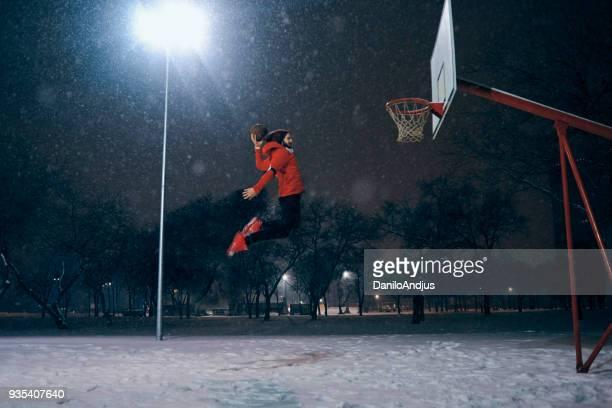 Athlet Mann Slam Dunks im Freien während schneit