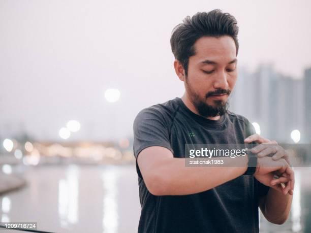 川の街でスマートウォッチを使用してアスリートの男。 - スポーツ チェックする ストックフォトと画像