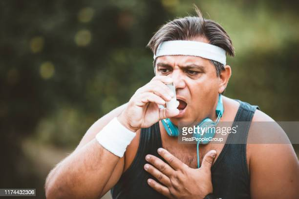 athlete mature overweight man using asthma inhaler outdoors. - asthma stock pictures, royalty-free photos & images