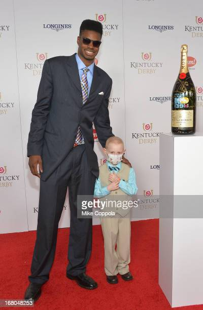 Athlete Nerlens Noel and Kelly Melton sign the Moet Chandon 6L for the Churchill Downs Foundation during the 139th Kentucky Derby at Churchill Downs...