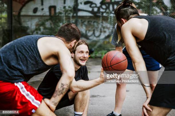 athlete offering basketball to teammate before the game begins - capitaine d'équipe photos et images de collection