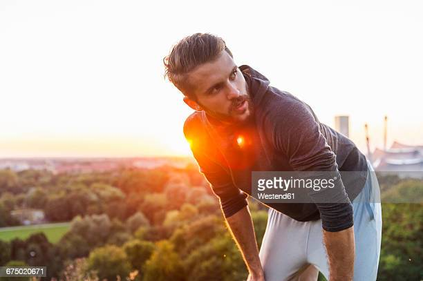 athlete on a hill having a break at sunset - sportlichkeit stock-fotos und bilder