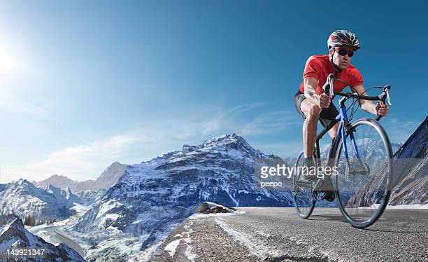 athlete on racing bike cycling through alpine mountains - european alps stock photos and pictures