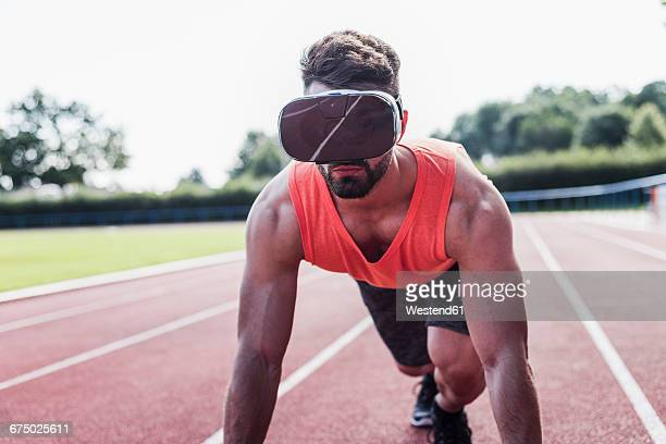 Athlete on tartan track wearing virtual reality glasses