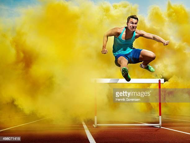 athlete over hurdle, in yellow smoke