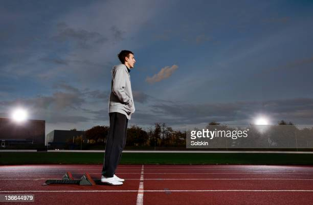 athlete preparing for run on stadium - forward athlete stock pictures, royalty-free photos & images