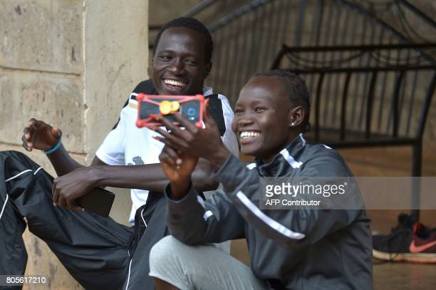 Athlete refugees from South Sudan Gai Nyang and Rose Nathike Lokonyen who is also an 800m Olympian at the Rio Olympic Games look at photos on May 12,...