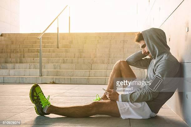 Athlete resting near a stadium entrance