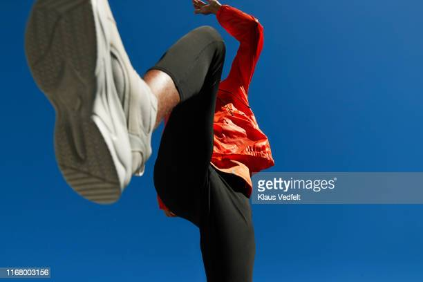 athlete running against clear blue sky on sunny day - sports shoe stock pictures, royalty-free photos & images