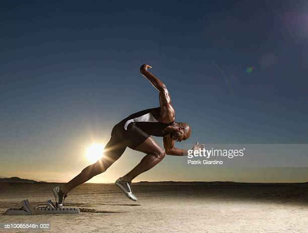 Athlete running from starting block at dusk, side view