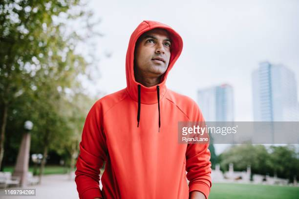 athlete running in bellevue city park - hooded top stock pictures, royalty-free photos & images