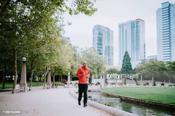 athlete running in bellevue city park - washington state stock pictures, royalty-free photos & images