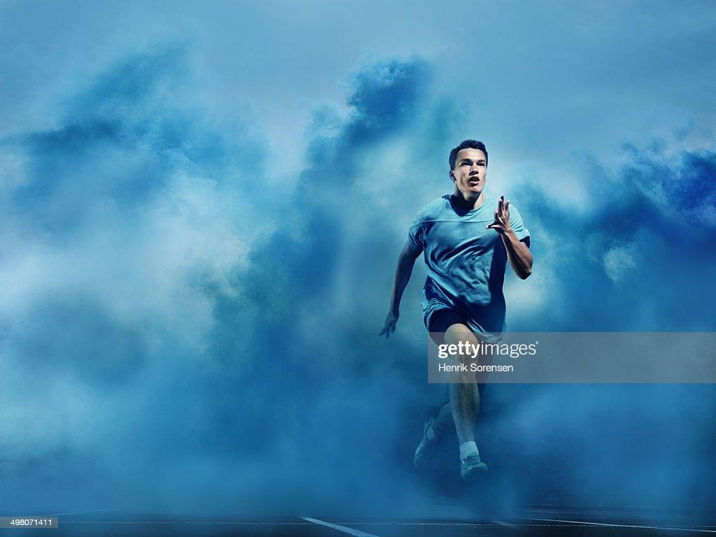 athlete running in blue smoke : Foto de stock