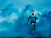 athlete running in blue smoke