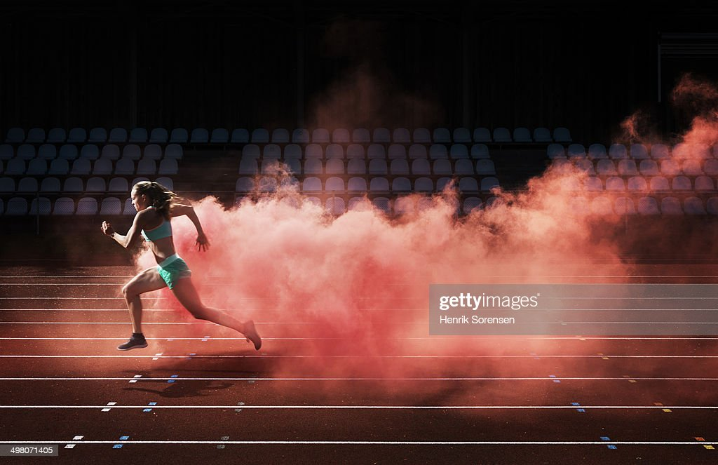 athlete running in red smoke : Stock Photo