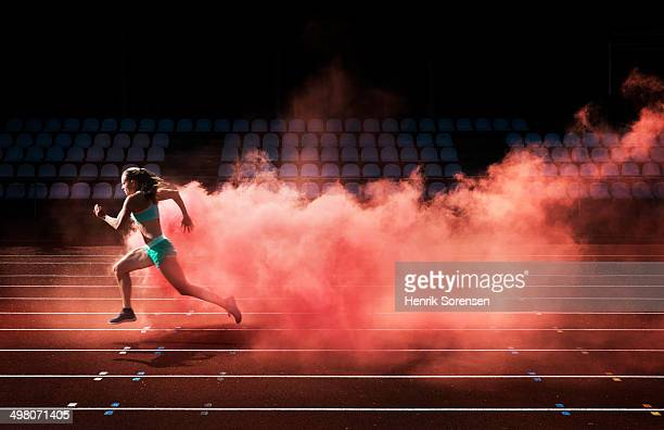 athlete running in red smoke - sportsperson stock pictures, royalty-free photos & images