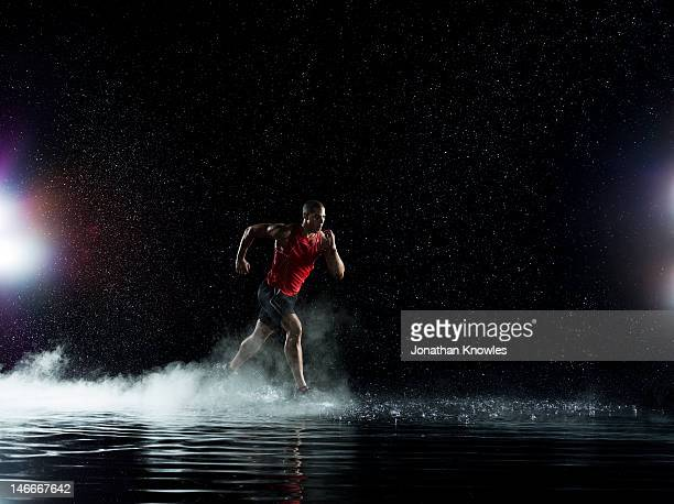 Athlete running in water in rain at night