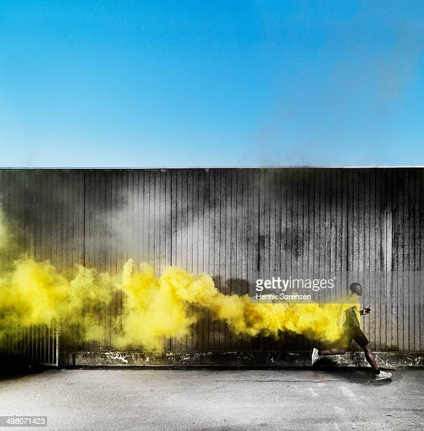 athlete running in yellow smoke