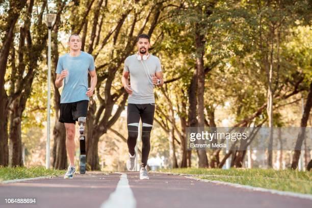Athlete running next to his amputee athlete friend
