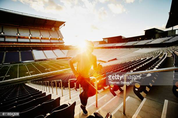 athlete running stairs in empty stadium at sunset - persistence stock pictures, royalty-free photos & images