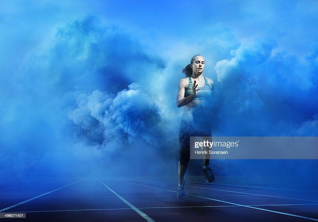 athlete running through blue smoke : Stock Photo