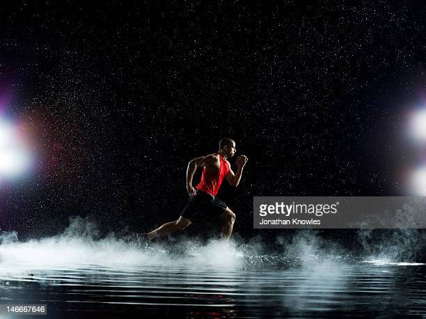 Athlete running through water, in rain at night