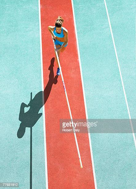 athlete running to do a pole vault - atletiek stockfoto's en -beelden