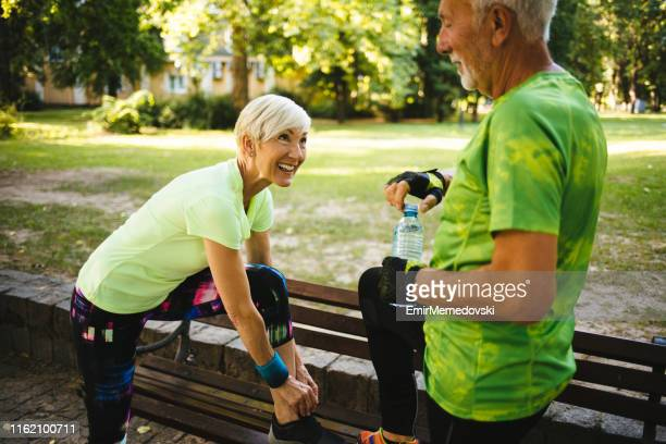 athlete senior woman tying sport shoe shoelace in the park - old man feet stock pictures, royalty-free photos & images