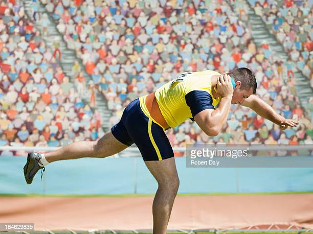 athlete shot putting in an arena - shot put stock pictures, royalty-free photos & images
