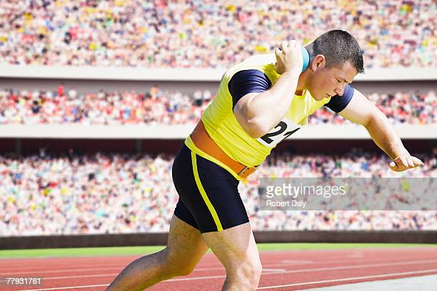 athlete shotputting in an arena - shot put stock pictures, royalty-free photos & images