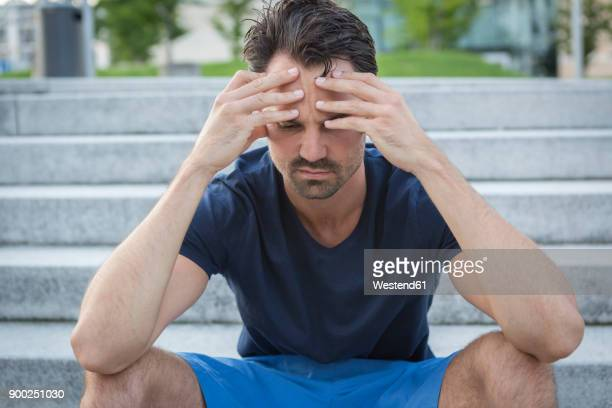 athlete sitting on stairs with hands on head, having a headache - 身体症状 ストックフォトと画像