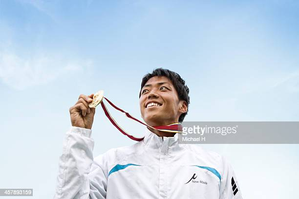 athlete smiling on podium with the medal