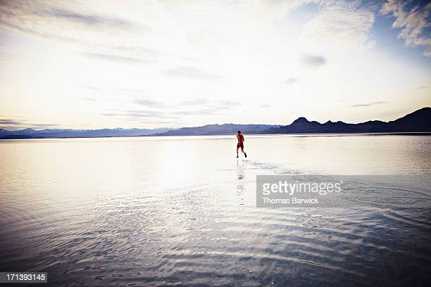 Athlete sprinting across surface of lake at sunset