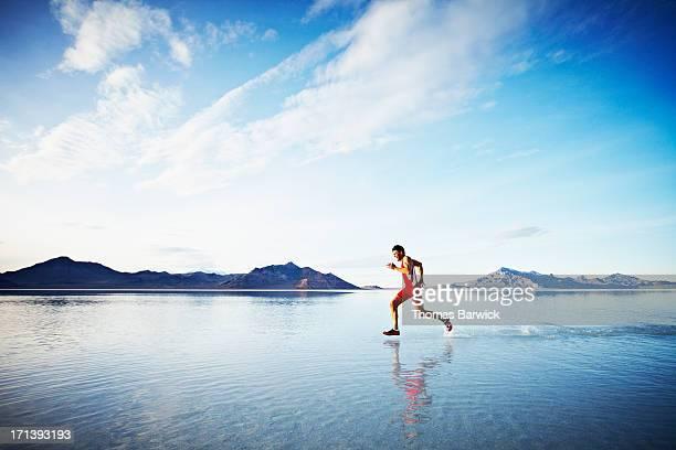 Athlete sprinting across surface of lake