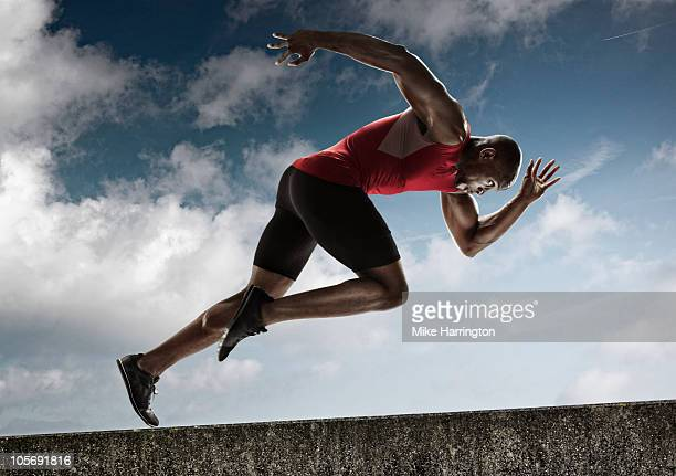athlete sprinting up steady incline - athletics stock pictures, royalty-free photos & images