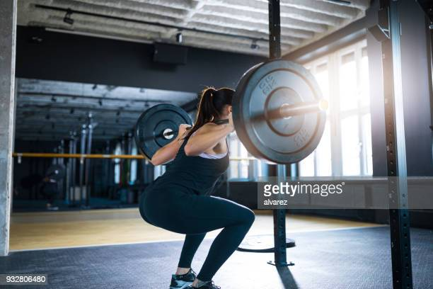 Athlete squatting while exercising with barbell