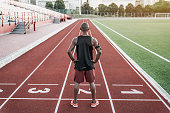 Athlete standing at the start line with hands on waist. Rear view of runner standing on running track.