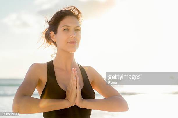 Athlete standing in prayer position at beach