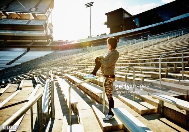 athlete stretching before workout in stadium - empty bleachers stock photos and pictures