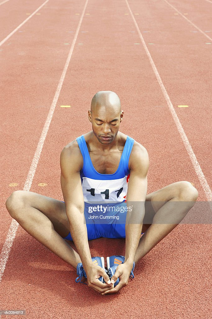 Athlete Stretching on a Running Track : Stock Photo