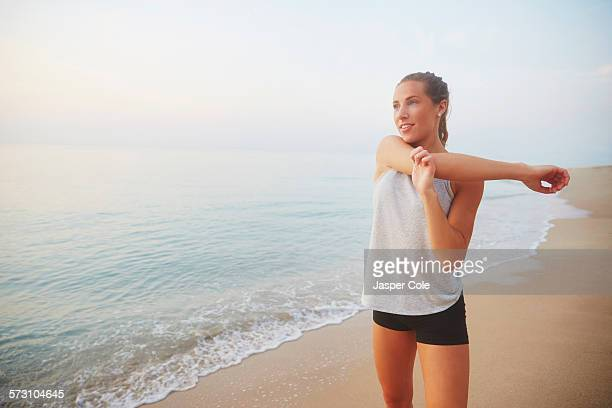 Athlete stretching on beach