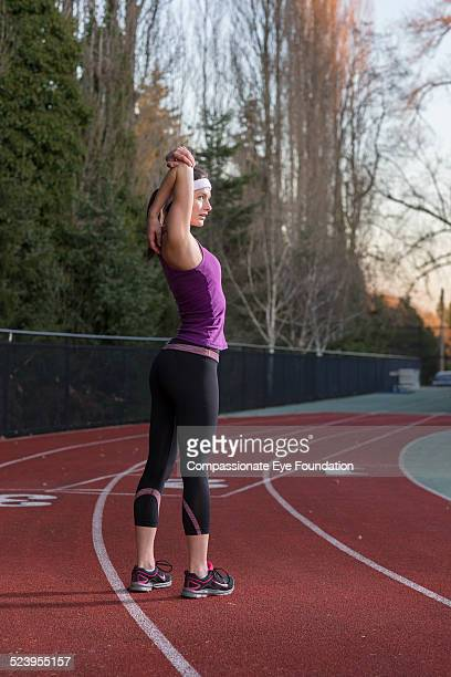 Athlete stretching on track