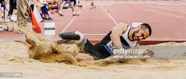 athlete suffering from amputee long jumping - 走り幅跳び ストックフォトと画像