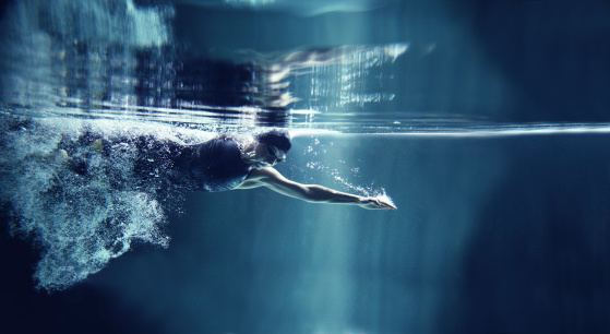Athlete swimming freestyle on blue background, underwater view 136694824